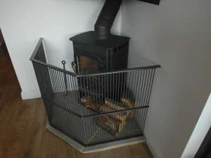 Image of a corner wood burner guard in situ around a wood burner in the home.