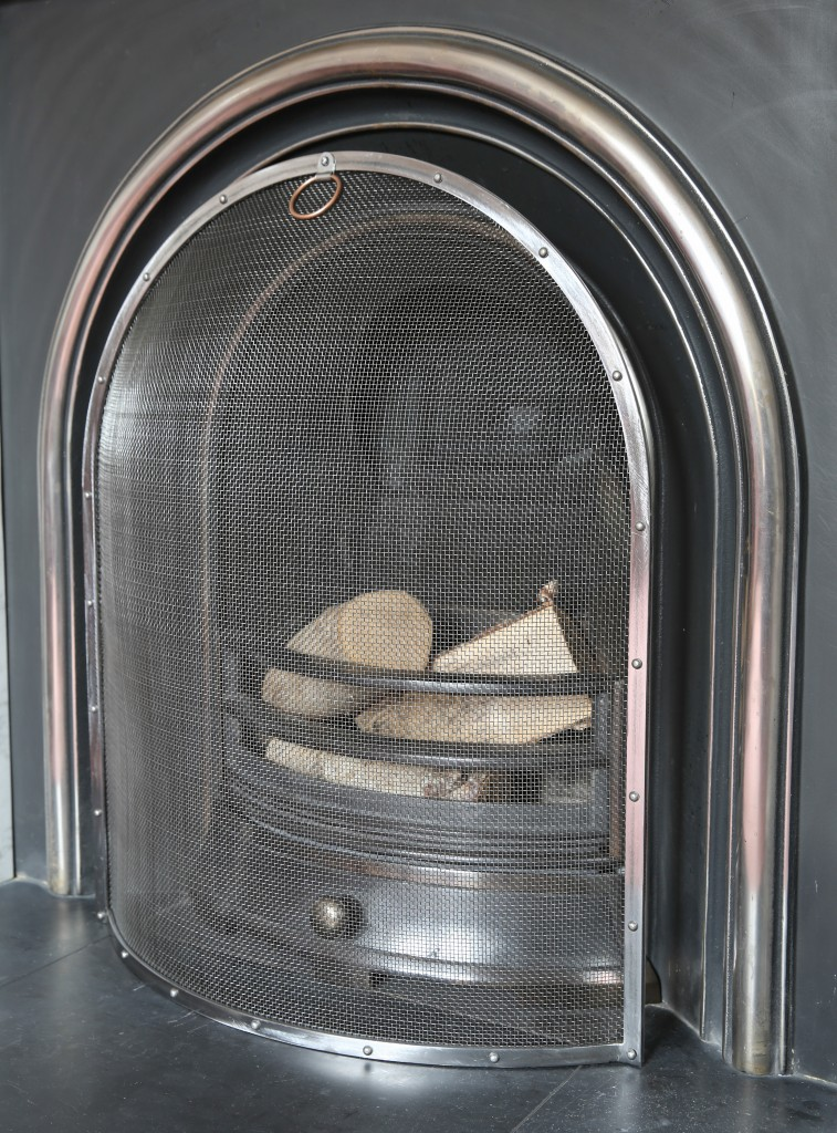 Small Arched Fire Guard in front of a cast iron victorian fireplace